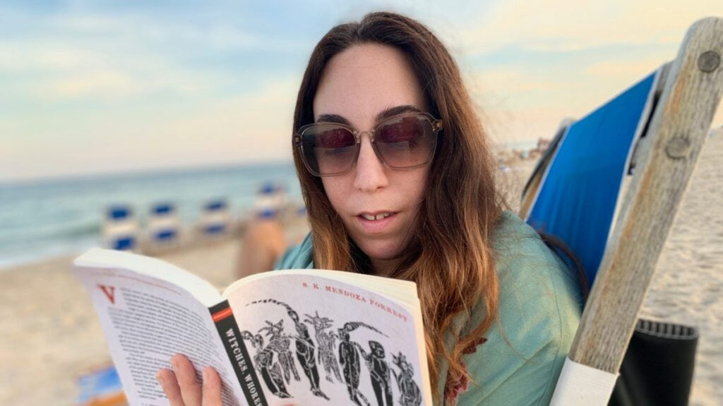 A fair-skinned woman with dark hair and sunglasses sitting in a chair on the beach reading
