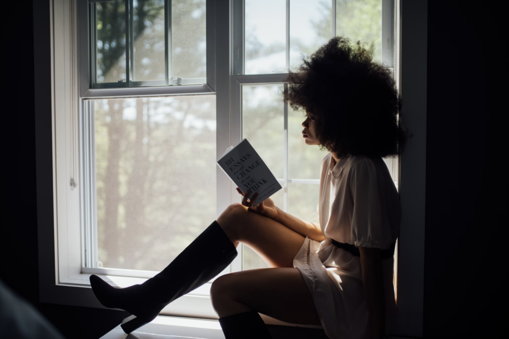 A brown-skinned woman with an afro sitting in a window reading a book