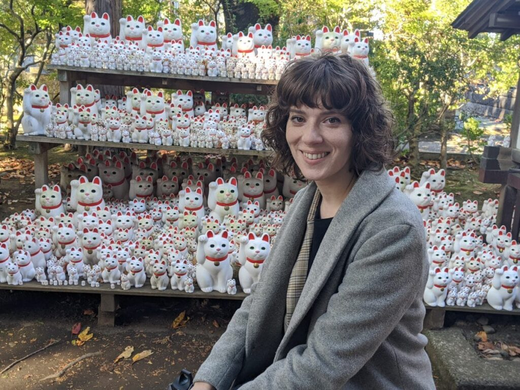 Woman with shoulder-length wavy brown hair smiling, sitting in front of several white porcelain cat stattues