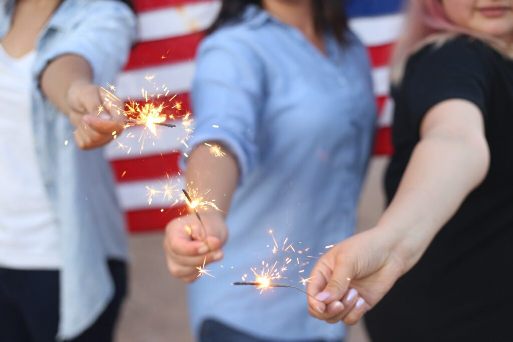 Three white women holding sparklers out