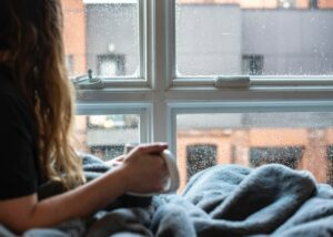 Light skinned woman holding coffee cup and looking out window