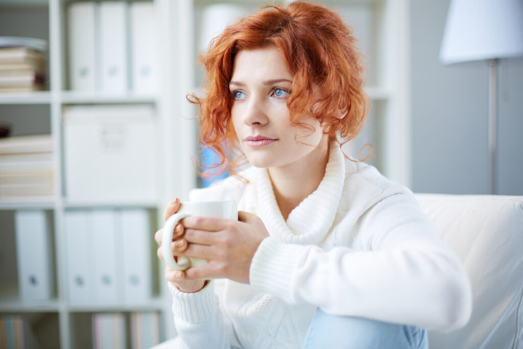A woman with red hair looking anxious and drinking.