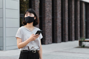 An Asian woman in a mask holding a phone and standing outside