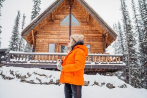 A woman in an orange winter coat standing outside of a winter cottage