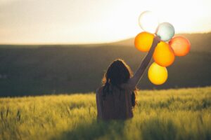 woman standing in a field holding up a bunch of balloons