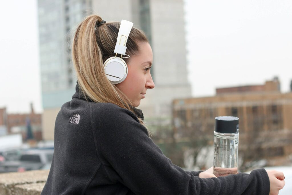 A pale-skinned young woman with blonde hair in a ponytail, listening to headphones and holding a water bottle