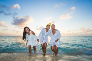 Three brown-skinned women in white outfits smiling and walking out of the ocean