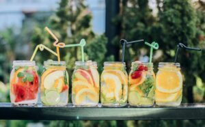Six mason jars filled with fruit-infused drinks