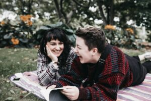 Two people laying on a blanket in the grass laughing