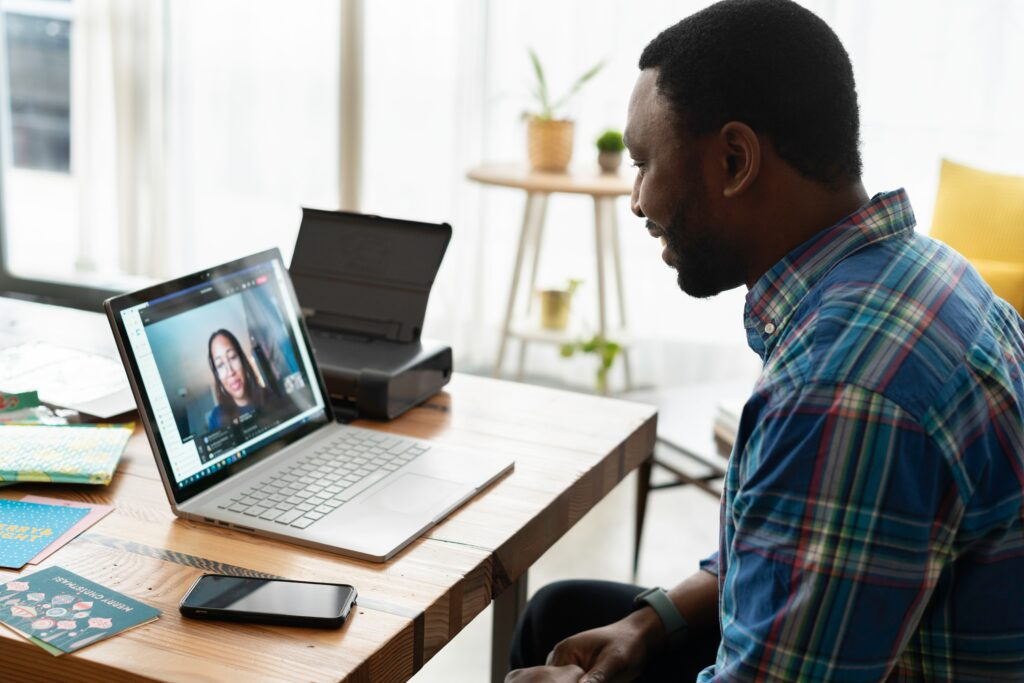 A Black man sitting at a desk and talking with a therapist online
