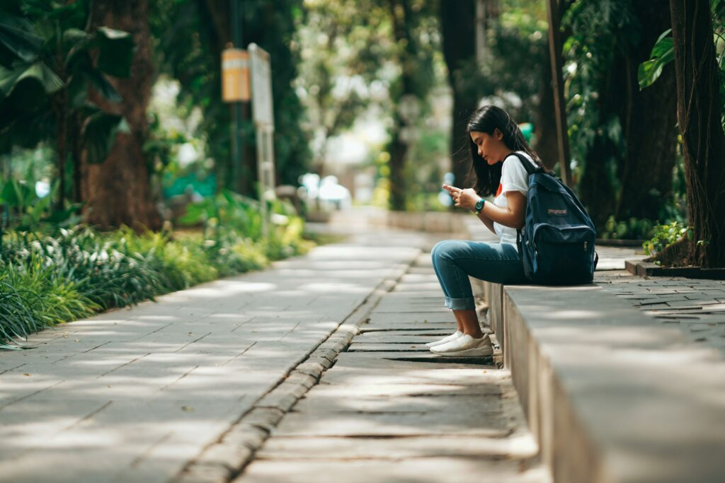 Woman sitting on curb looking at her phone