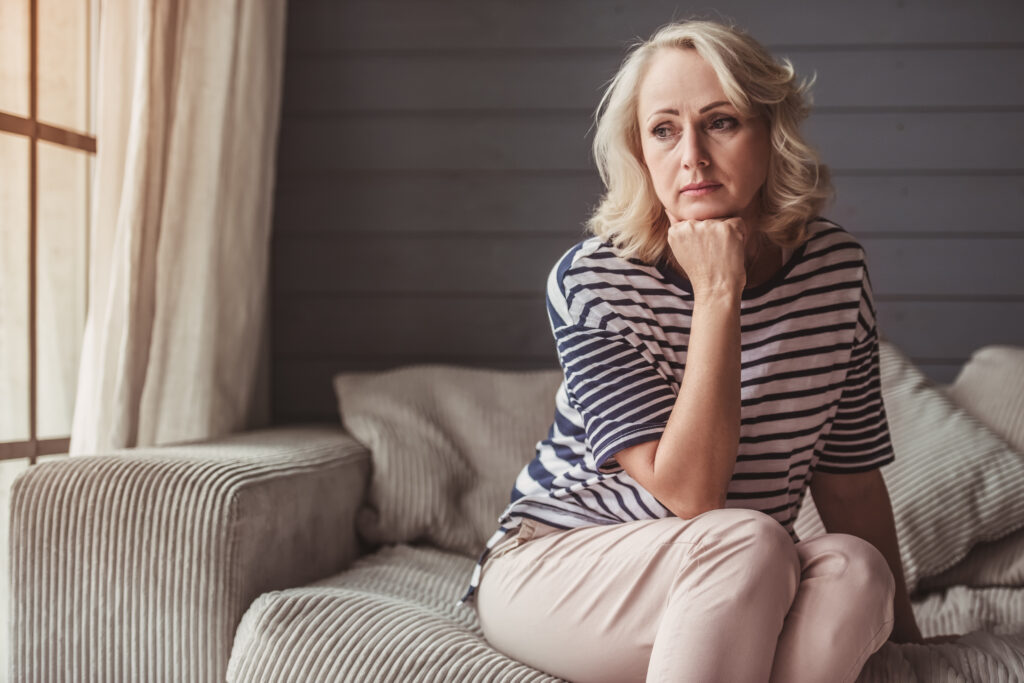 Sad older woman sitting on a couch and thinking about her alcohol use