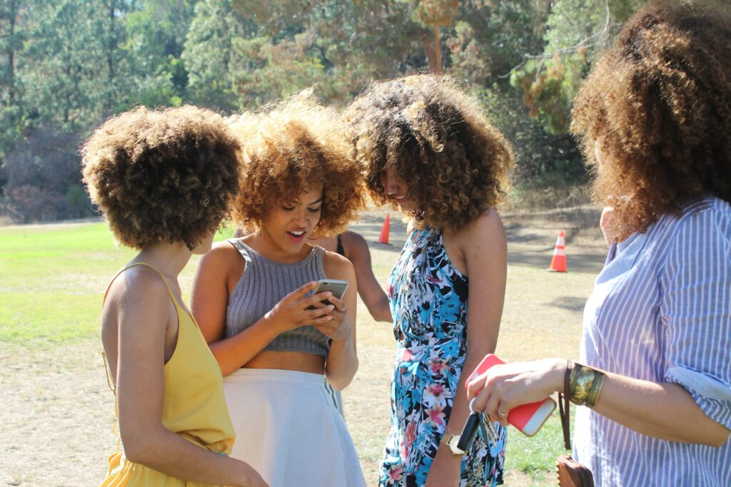 Four brown-skinned women with curly brown hair standing around each other looking at a cell phone