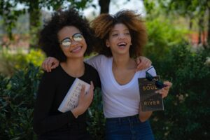 Two brown skinned women smiling and holding books