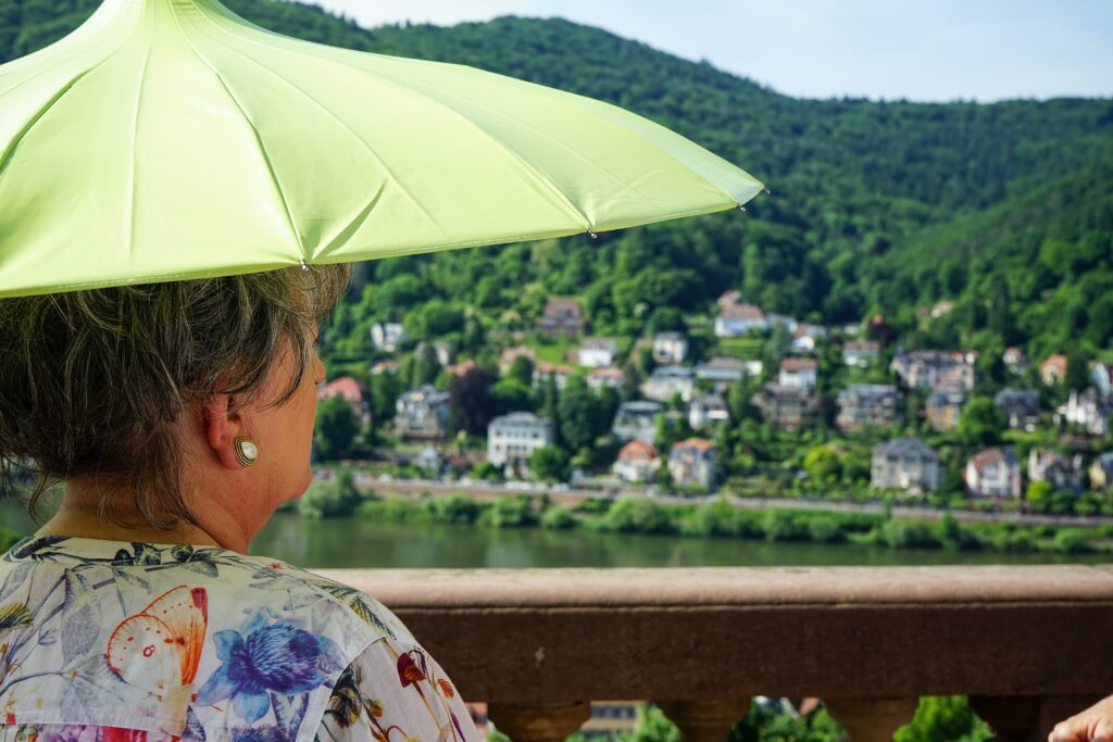 Gray haired woman with green umbrella looking out onto a wooded town